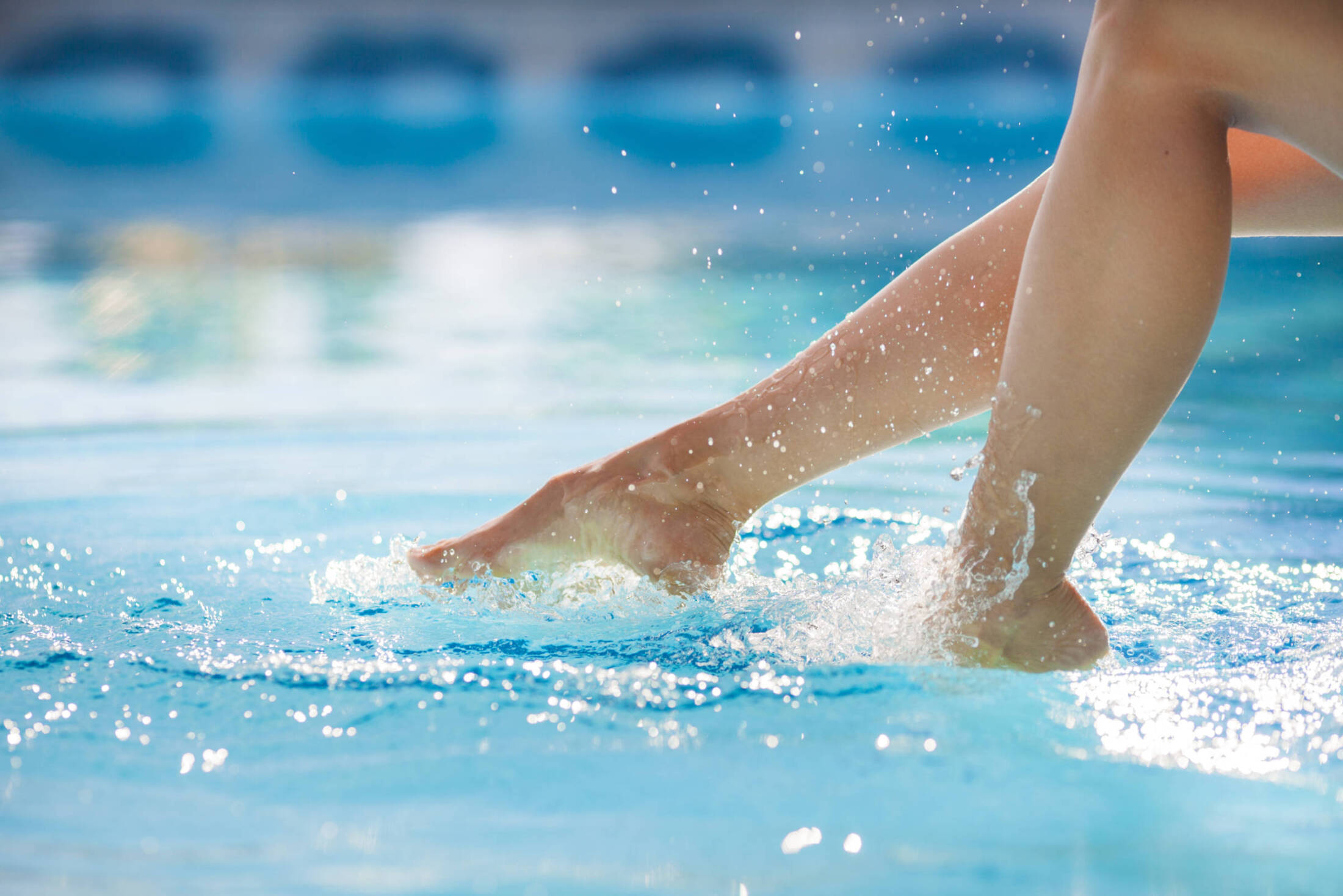 Woman's Feet Splashing The Pool Water