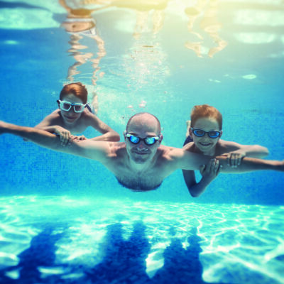 Father and sons playing underwater in resort pool. Family is playing underwater superheroes. Nikon D850